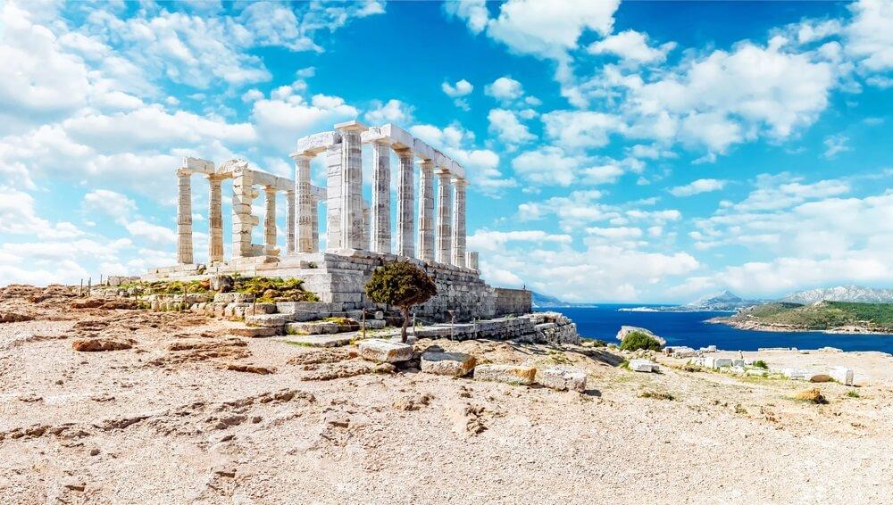 et historische Athene in Griekenland. Het beroemde Pantheon staat op een heuvel met daarachter de oceaan. Blauwe lucht met wolkjes op de achtergrond.