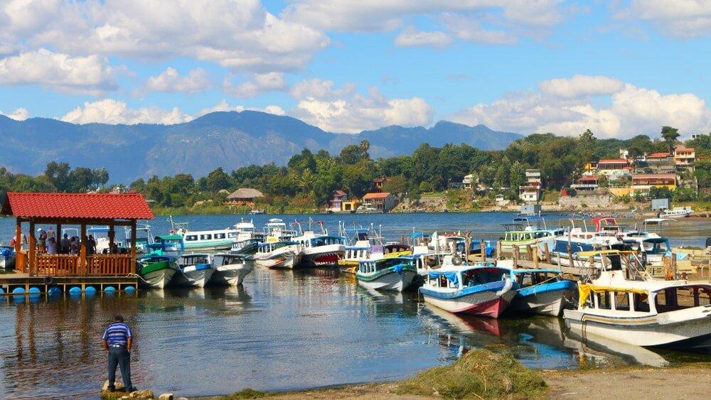 Santiago Atitlan, Guatemala haven. Kleurrijke bootjes dobberen in het water. Man staan aan de oever.