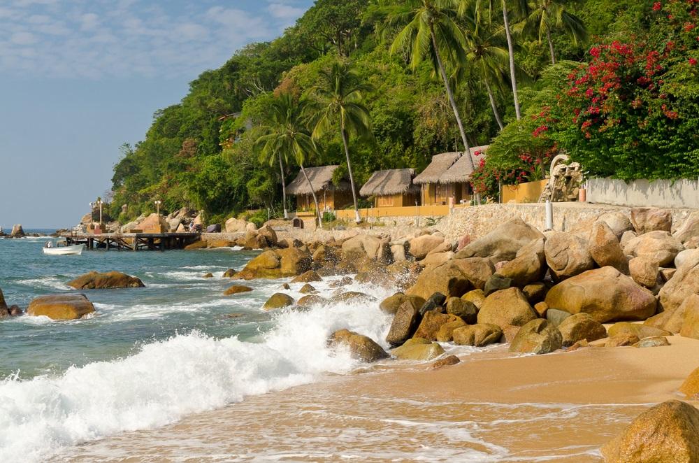 Ruige zee met rotsen en links groene heuvels met houten cabins, daartussen palmbomen. Strakblauwe lucht.