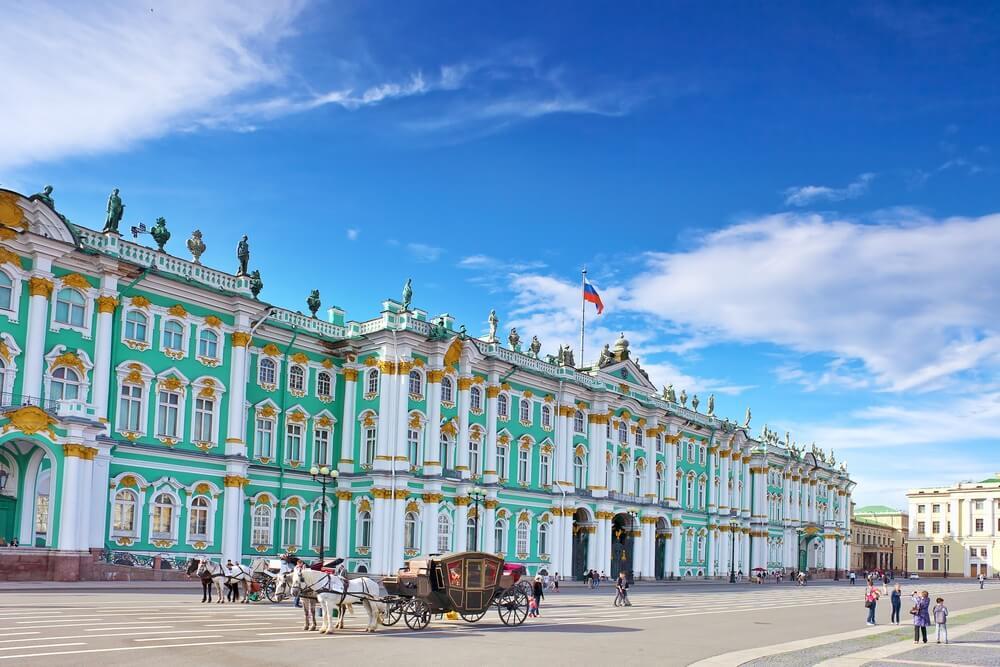 Het Winterpaleis in Sint Petersburg. Blauwe en witte kleuren, koets met paarden daarvoor. Blauwe lucht met enkele wolken.