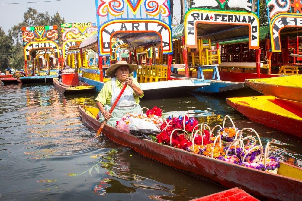 Gekleurde bootjes op de Xochimilco rivier bij Mexico stad. Mexicaanse man vaart in zijn boot met gekleurde bloemen om te verkopen.