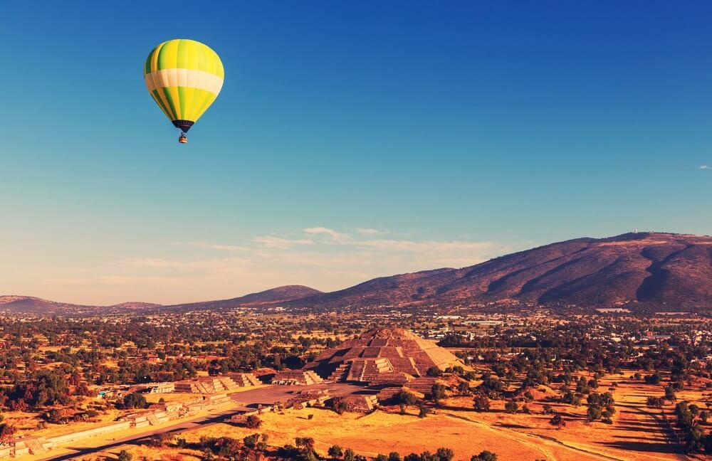 Een gele ballon in de strakblauwe lucht over het landschap en de oude ruïnestad Teotihuacán, Mexico.
