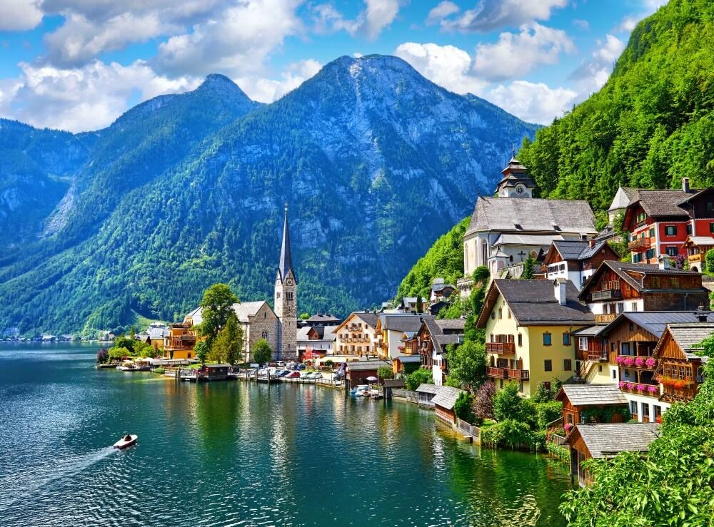 Hallstattersee in Oostenrijk, dorpje rechts tegen groene helling aan. Hoge bergen op de achtergrond. Wolkjes met blauwe lucht.