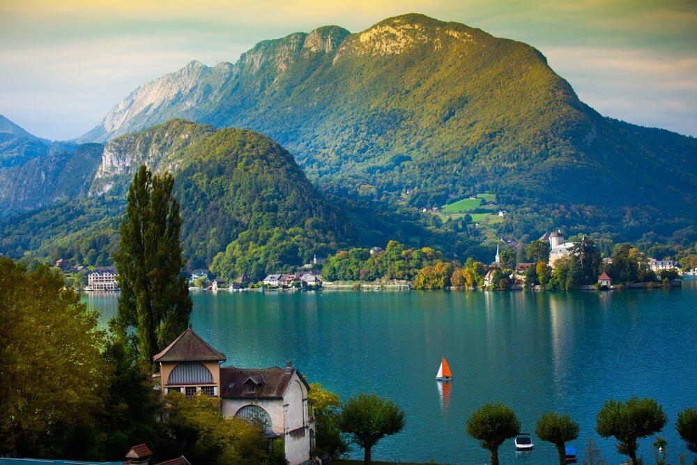 Het meer van Annecy, Frankrijk. Hoge bergen op de achtergrond, oud huis op de voorgrond en rood-witte zeilboot op het water.