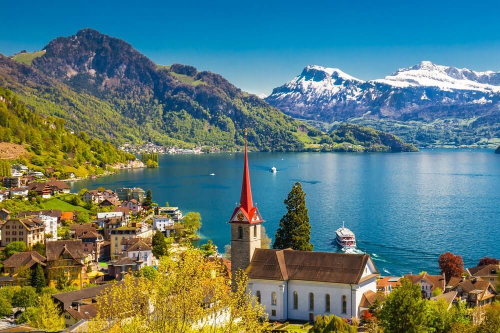 Vierwoudstedenmeer, Zwitserland. Kerk op de voorgrond, dorpje links. Besneeuwde bergen en groene bergen op de achtergrond. Strakblauwe lucht.