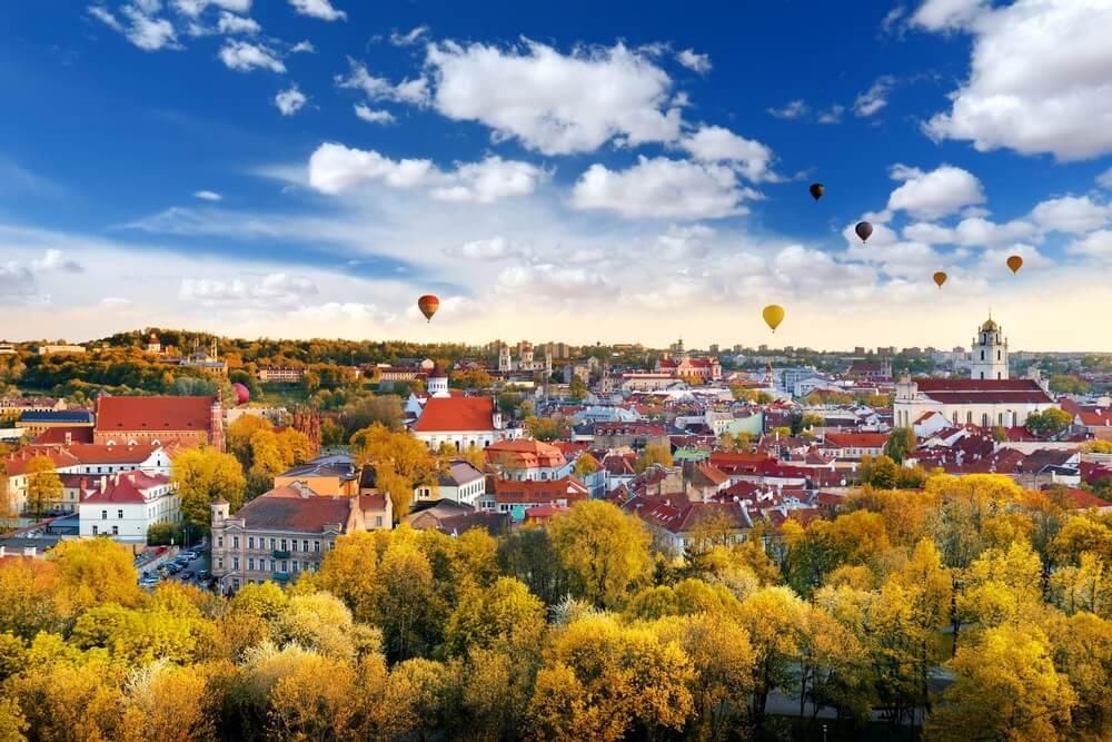 Uitzicht over Vilnius, Litouwen. Luchtballonnen in de lucht, blauw met witte wolkjes, groene bomen en rode daken van de huisjes.