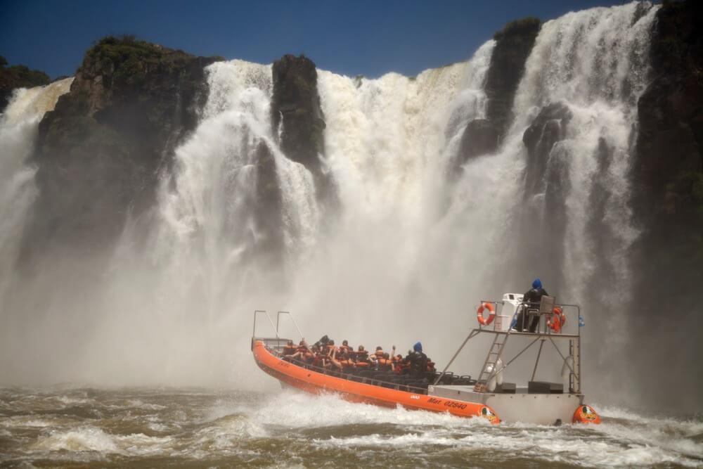 Mensen in boot om de watervallen van dichtbij te zien - Iguazu Waterfalls National Park, een wonder van de natuur tussen Brazilië en Argentinië.