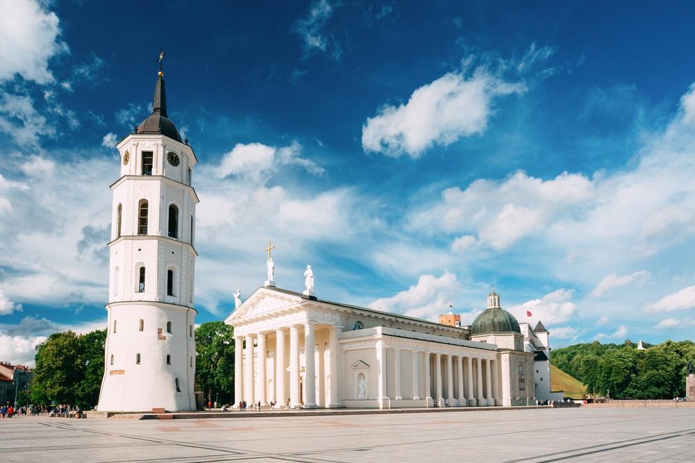 Vilnius, Litouwen. Uitzicht op de klokkentoren en gevel van de kathedraal basiliek van St. Stanislaus en St. Vladislav Op het plein van de kathedraal, beroemde bezienswaardigheid, showplace In zonnige zomer onder blauwe hemel met wolken.