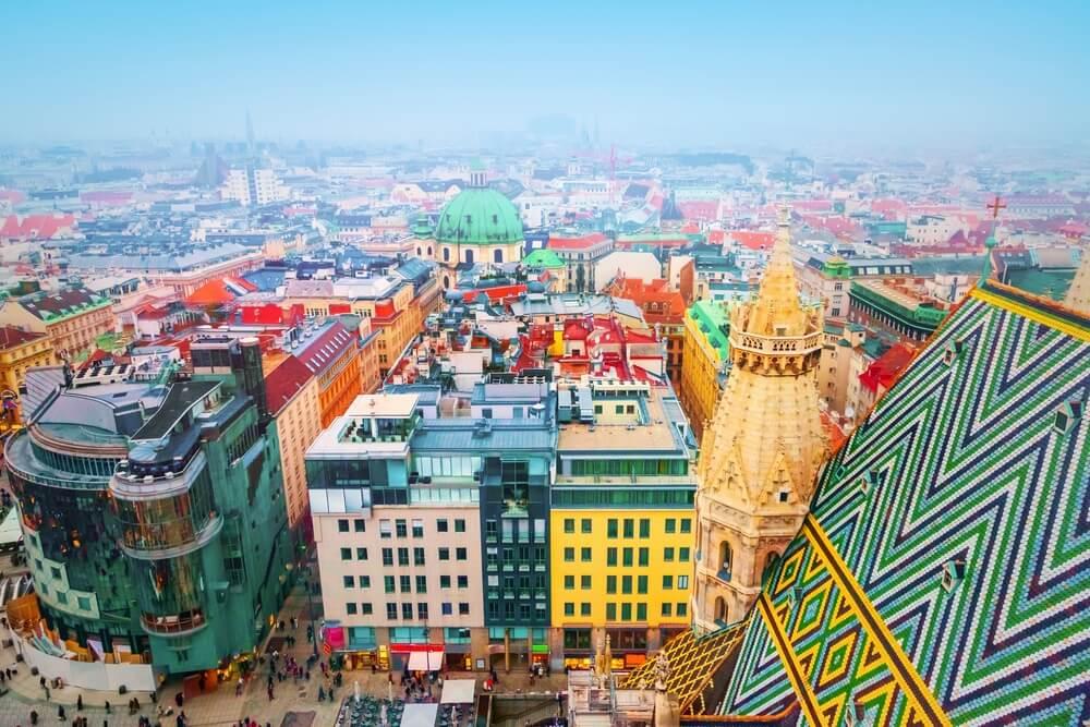 Luchtfoto van Wenen, Oostenrijk. Veel gekleurde gebouwen, mensen die door de straten lopen en mist in de achtergrond.