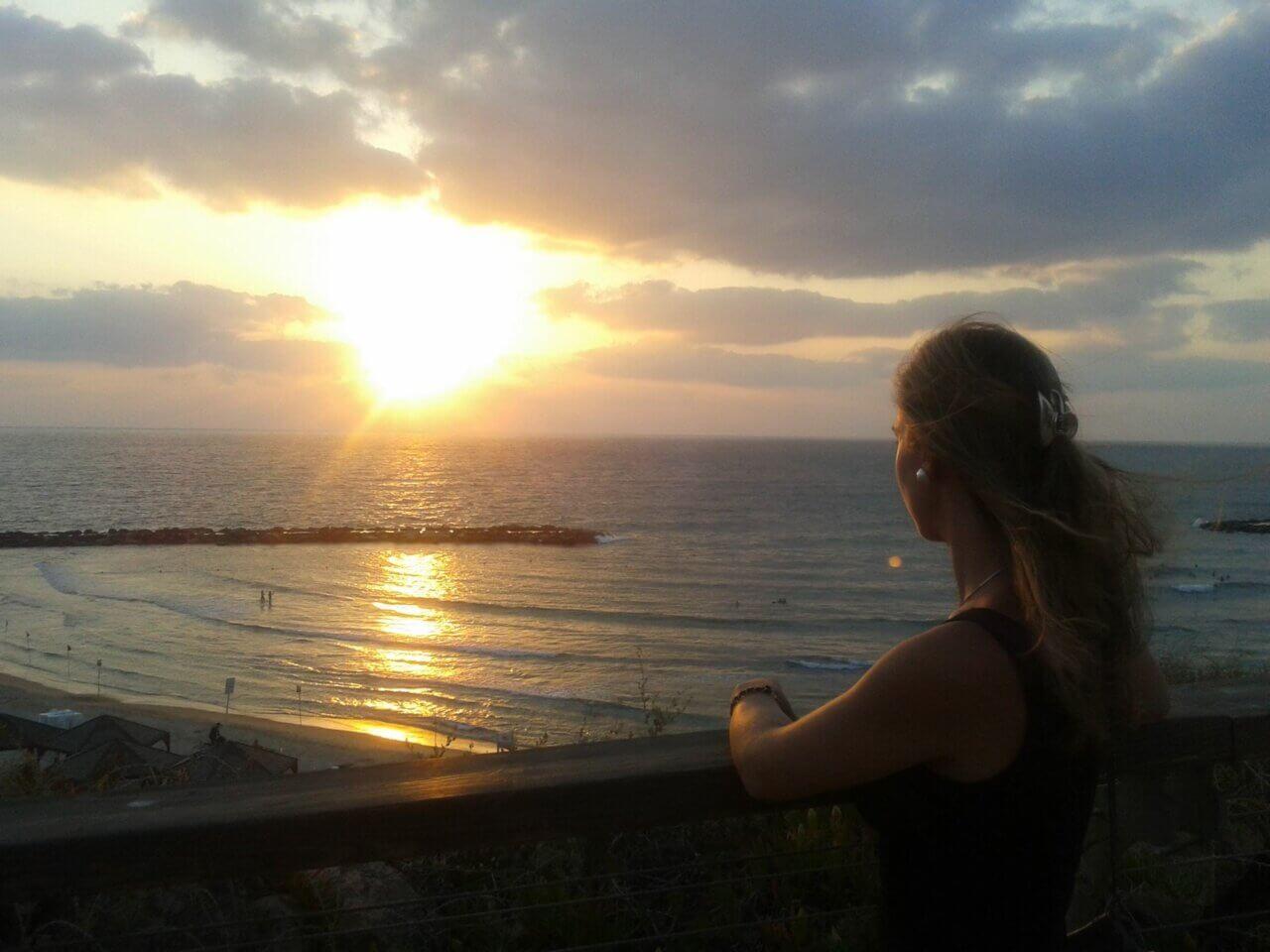 Vrouw kijkt tijdens de zonsondergang over de zee, leunt met haar arm op een balustrade.