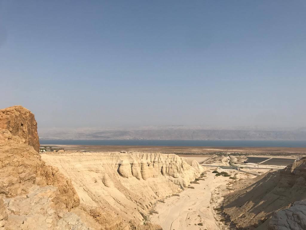 Woestijnlandschap met daarachter de dode zee en aan de overkant Jordanië. Strakblauwe lucht.