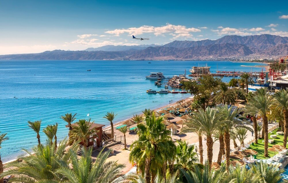 Boulevard van Eilat, Israël. Azuurblauwe zee daarnaast en bergen op de achtergrond. Vliegtuig in de lucht.