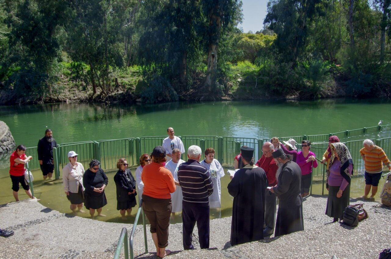 De Jordaan rivier met daarvoor een stuk of 20 mensen die in de rij staan om gedoopt te worden.