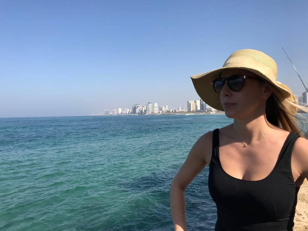 Vrouw kijkt uit over de zee in Tel Aviv met de skyline van de stad op de achtergrond.