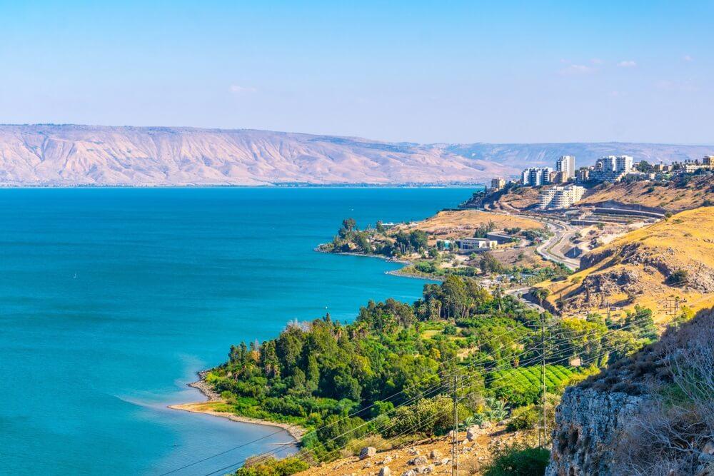 Meer van Galilea, Israël. Azuurblauw water met rechts de stad Tiberias.