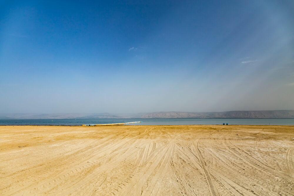 Breed zandstrand aan het meer van Galilea, strakblauwe lucht.
