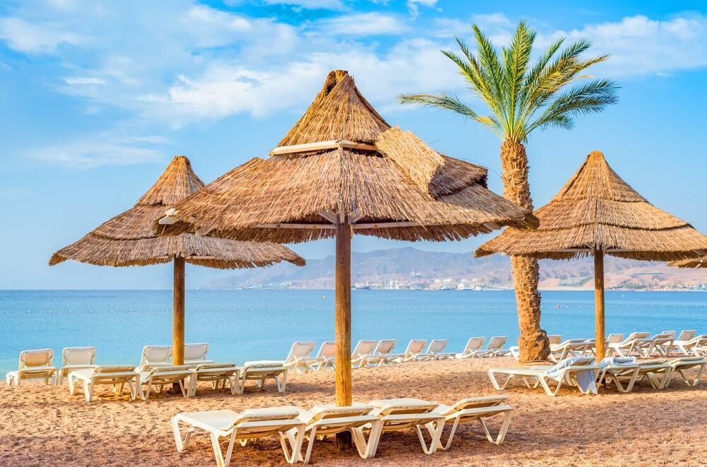Strand in Eilat, Israël. Drie bamboe parasols en een palmboom. Witte ligbedjes.