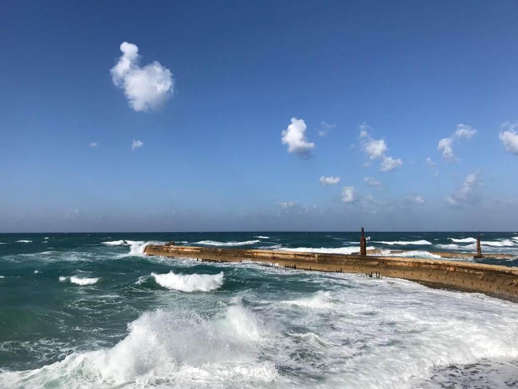 Ruige zee aan de kust ban Akko, witte schuimkoppen, links een steiger die in de zee loopt. Blauwe lucht met enkele wolkjes.