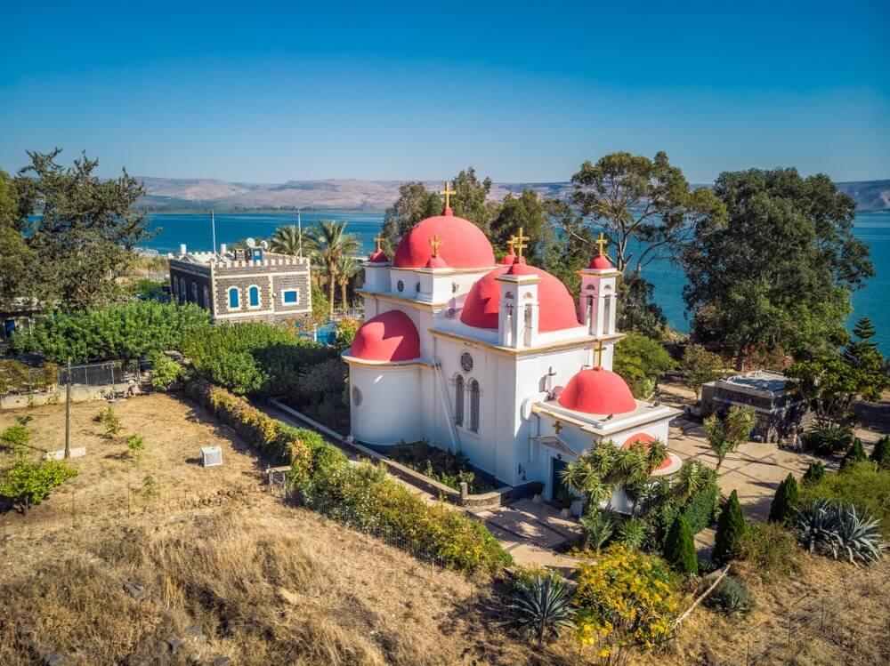 De Grieks-Orthodoxe kerk van de 12 Apostelen aan het meer van Galilea, Israël genomen vanaf de Kinneret Trail op een heuvel.