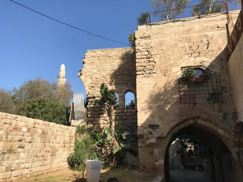 Oud gebouw in Akko, Israël met een kleine doorgang voor voetgangers. Strakblauwe lucht.