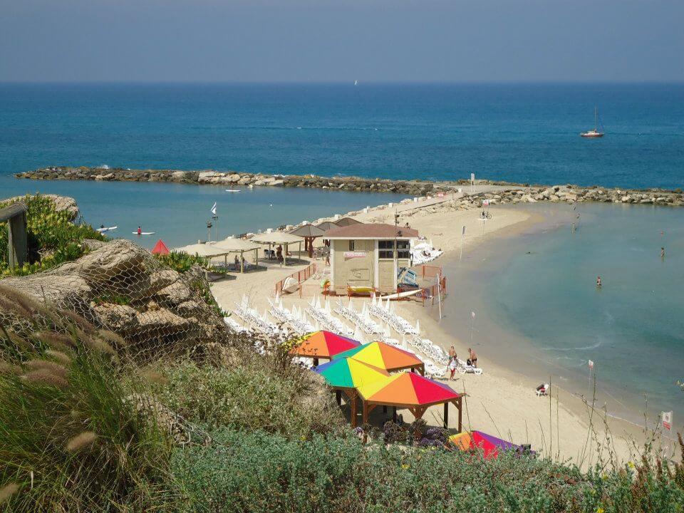 Uitzicht van het strand in Tel Aviv. Kleine inham met een paar parasols en gekleurde prieeltjes op de heuvel.