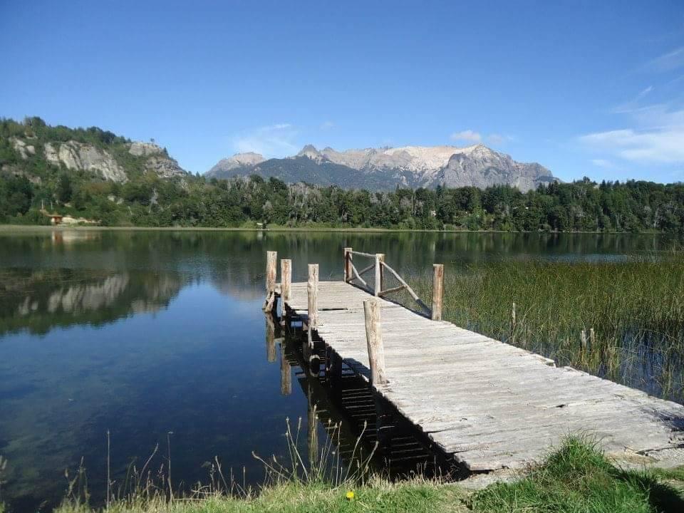 Meertje in Bariloche, met houten steiger over het water en hoge bergen aan de horizon.
