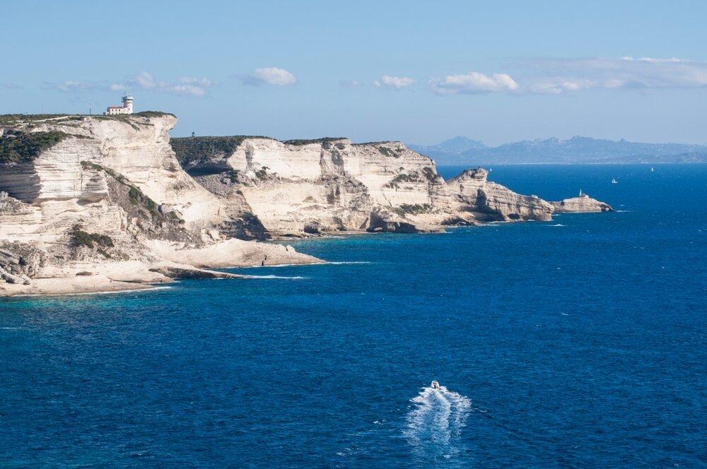 Corsica: de adembenemende witte kalkstenen kliffen van Bonifacio in het International Bouches de Bonifacio marine park, natuurreservaat opgericht in 1993, met uitzicht op de vuurtoren van Cape Pertusato