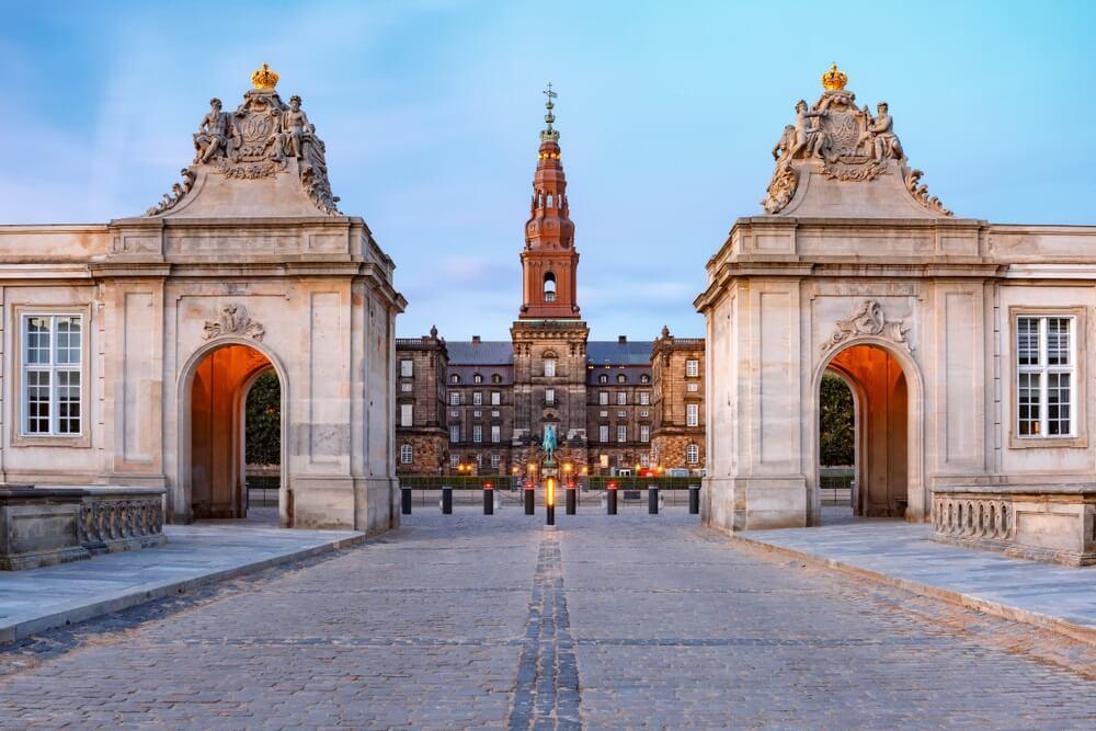 De hoofdingang van Christiansborg met de twee Rococo-paviljoens aan elke kant van de Marmeren Brug tijdens het ochtendblauwe uur, Kopenhagen, hoofdstad van Denemarken
