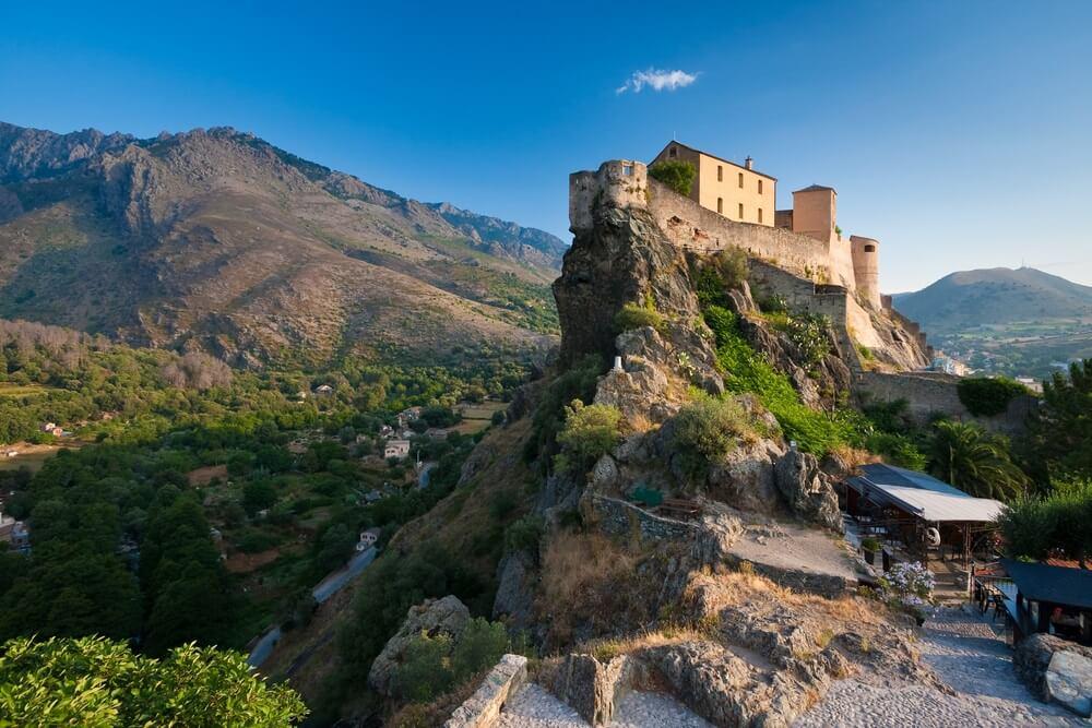 De citadel van het bergdorp Corte, Corsica, gebouwd op een hoge rots. Bergen op de achtergrond en een strak blauwe lucht.