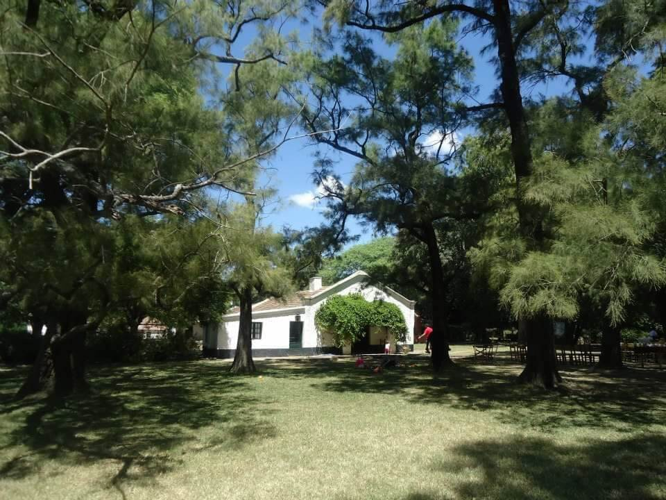 Estancia la Portena, op de Pampas in Buenos Aires. Witte boerderij omringt door bomen.