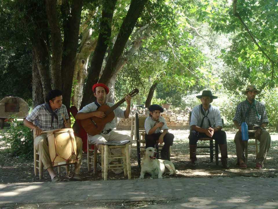 vijf gaucho's zitten op houten stoeltjes en maken live muziek bij estancia la Portena, Buenos Aires.