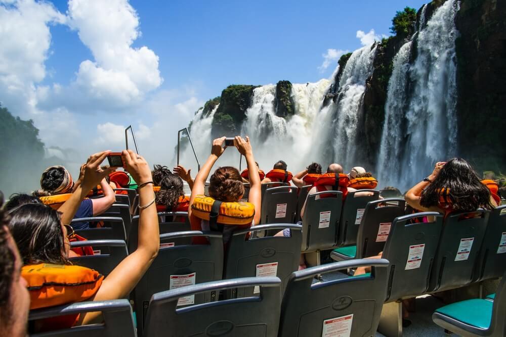 Toeristen zitten met hun rug naar de camera toe in een boot, die langs de watervallen vaart in Iguazú, Argentinië.