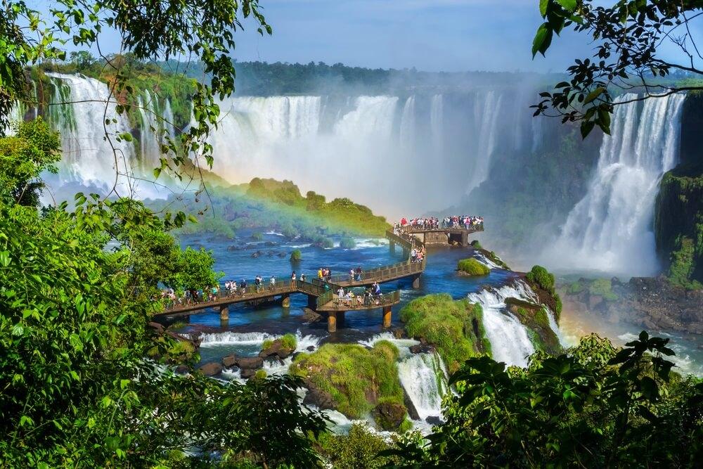 Argentijnse kant van Iguazú; toeristen lopen over een houten loopbrug langs de watervallen af.