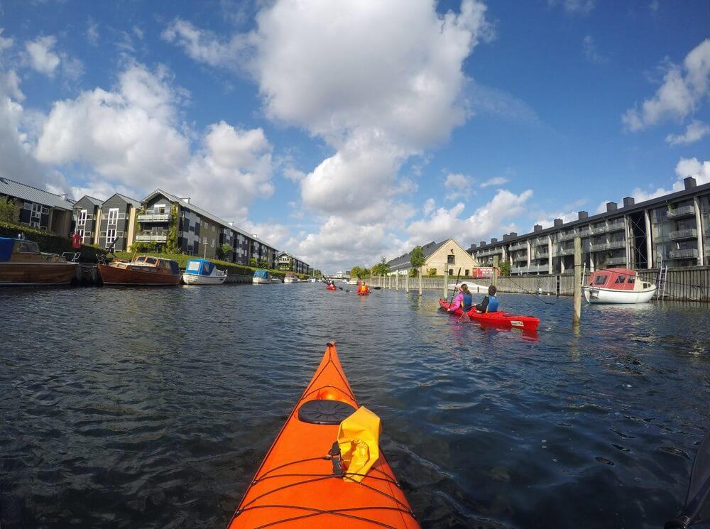 Kajakken door de grachten van Kopenhagen, Denemarken. Oranje kayak is in zicht.