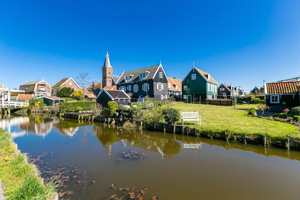 Typisch Nederlandse dorpsscène met blokhuizen op het eiland Marken in Nederland, Holland. Blauwe luct en gracht op de voorgrond.
