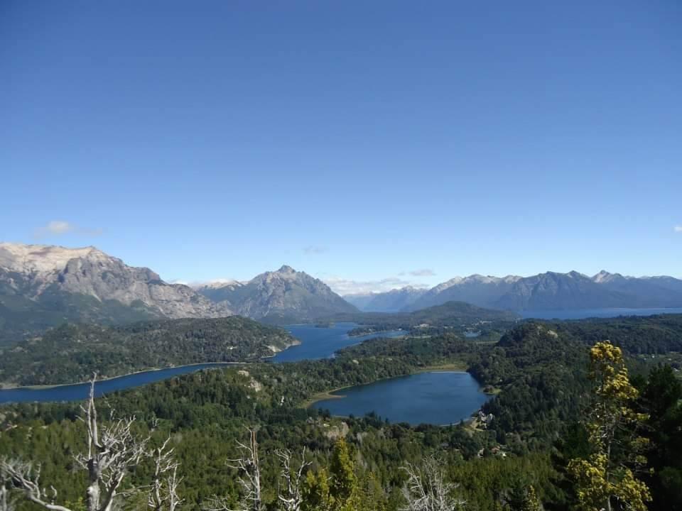 Het uitzicht vanaf Cerro Campanerio, Bariloche. Verschillende meren, hoge bergen op de achtergrond en groene bossen.