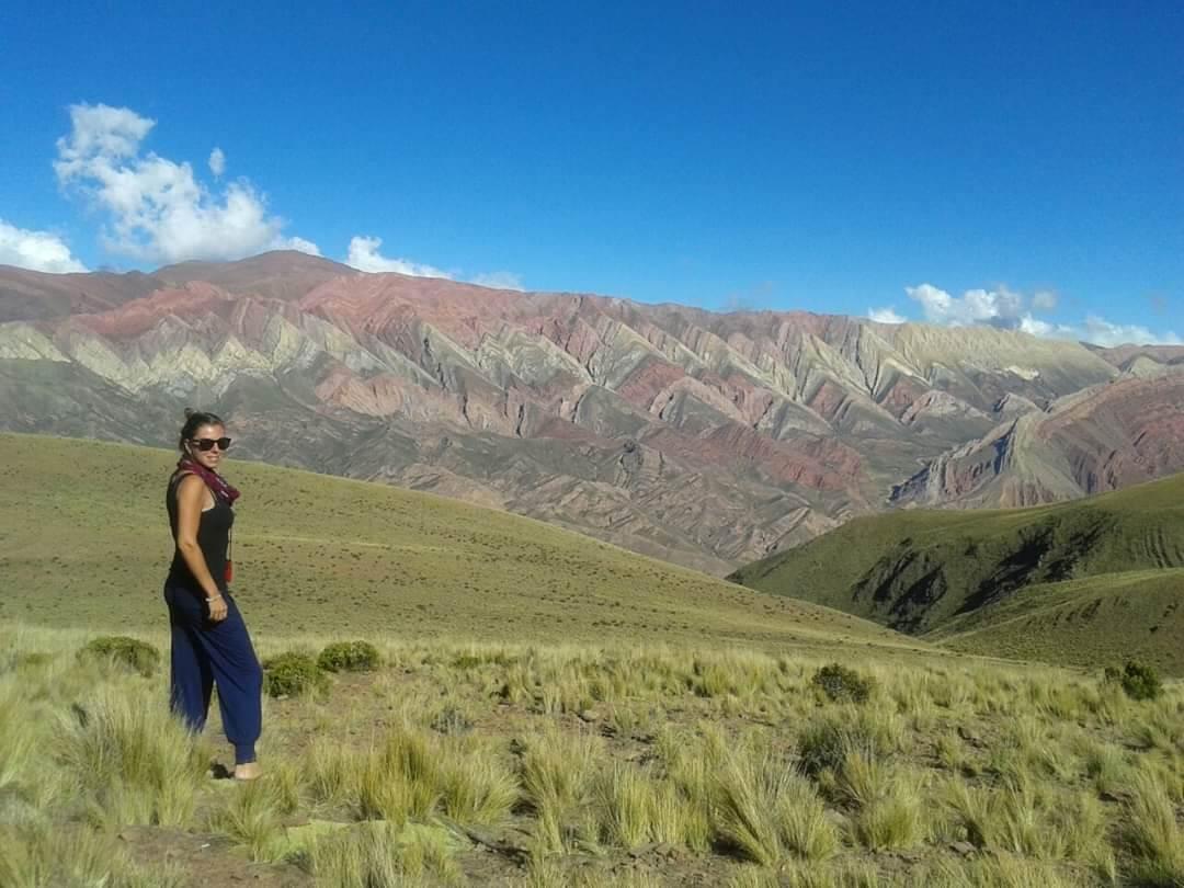 Quebrada de Humahuaca. Vrouw staat links in beeld, lacht in de camera. Strakblauwe lucht.