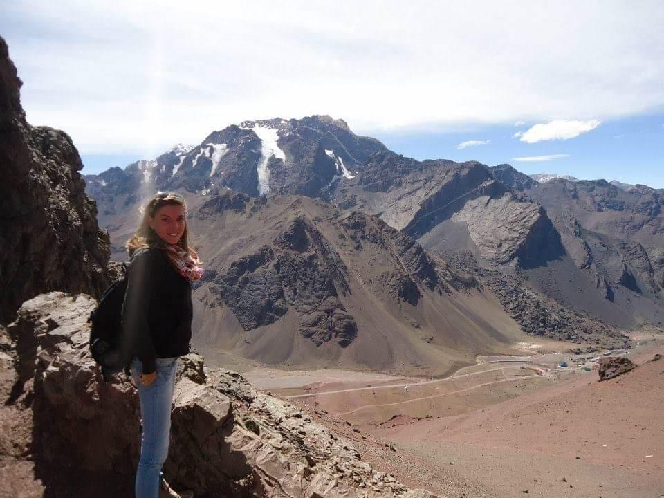 Vrouw staat links in beeld met op de achtergrond ruige kale bergen van de Andes, beetje sneeuw op de top.