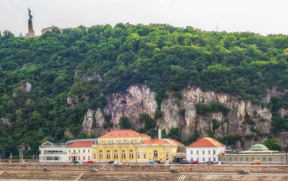 De mooi gelegen Rudas baden in Boedapest, tegen een groen begroeide rots aan.