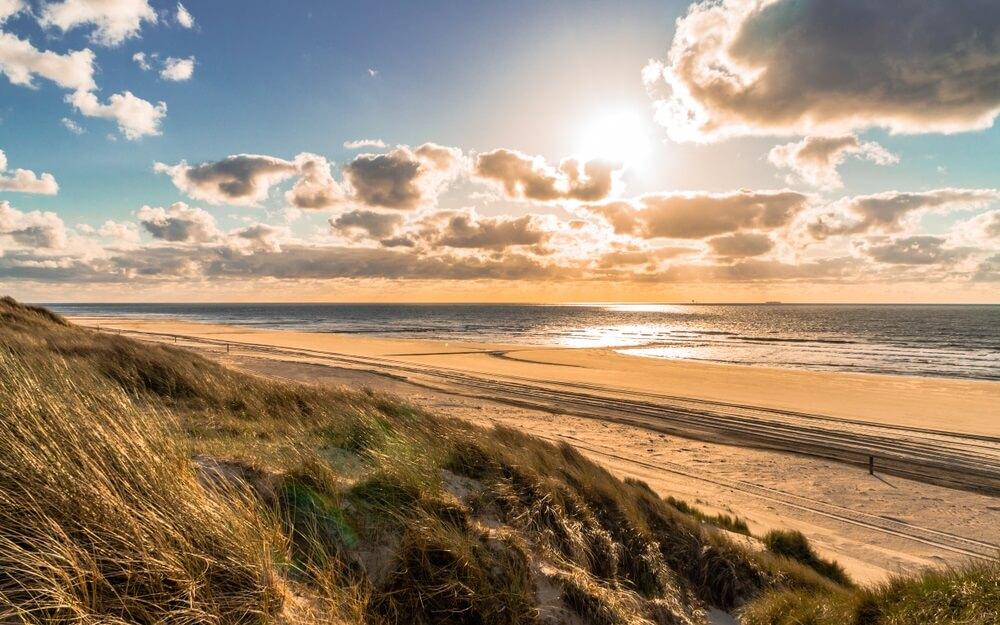 Wild Noordzee kust zonsondergang zeegezicht met brede zandige kustlijn en hoog gras leunend en geblazen met een sterke onshore wind en dramatische bewolkte blauwe hemel op Vlieland eiland in Nederland.
