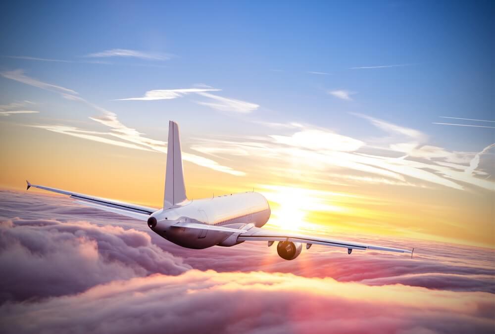 Commercieel vliegtuig vliegt boven wolken in dramatische zonsondergang licht. Zeer hoge resolutie van het beeld