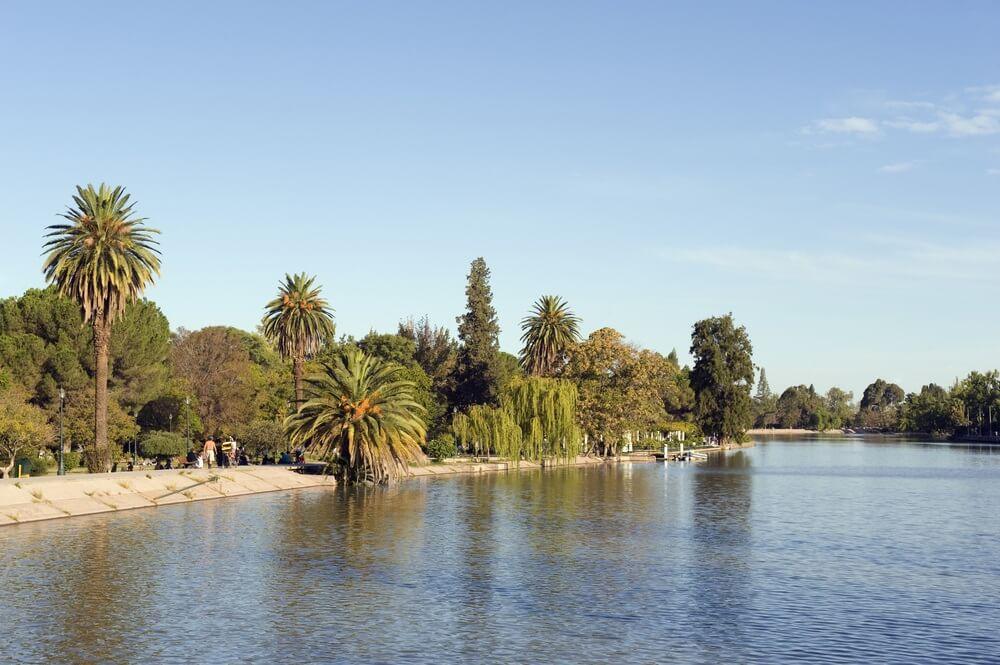 Stadspark in Mendoza met zijn mooie rivier. Groene bomen aan weerszijden en een boulevard.