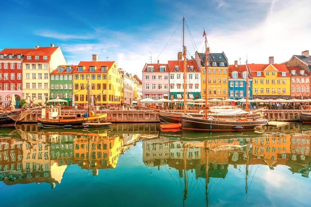 De haven van Kopenhagen met bootjes aan de waterkant. Gekleurde huizen aan de oevers die weerspiegelen in het water. Blauwe lucht.