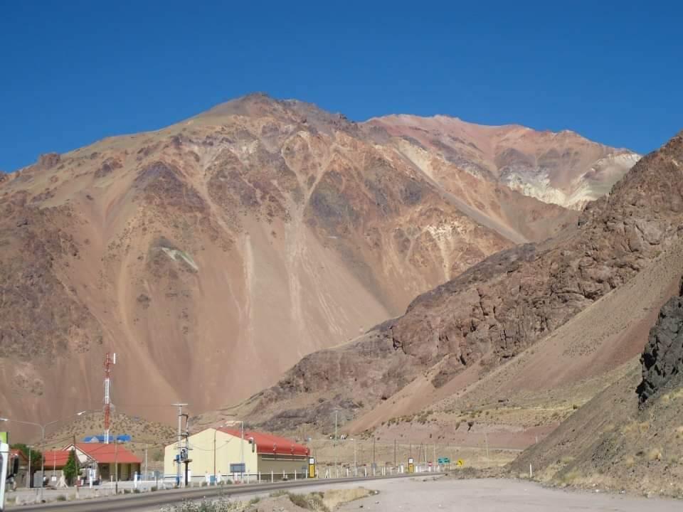Omgeving van Mendoza, uitzicht tijdens een tour. Immens hoge bergen beslaan bijna het hele beeld. Weg restaurantje op de voorgrond.
