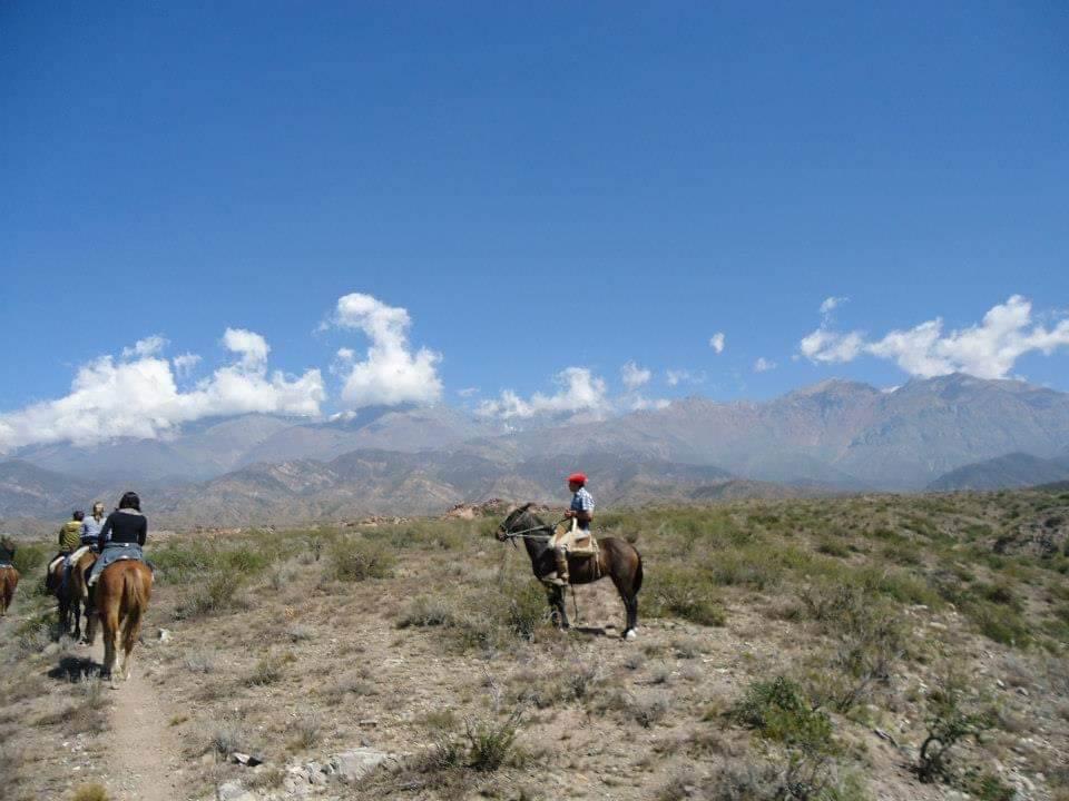 Paardrijd tour met de gaucho's in de het Andes gebergte. Gaucho zit op zijn paard in het midden van de afbeelding, aan de linkerkant rijden 3 toeristen op hun paard.