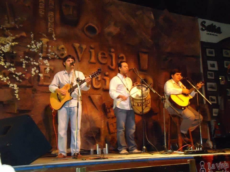 Live muziek in een Pena in Salta stad. 3 muziekanten staan op het podium met gitaar en microfoon.