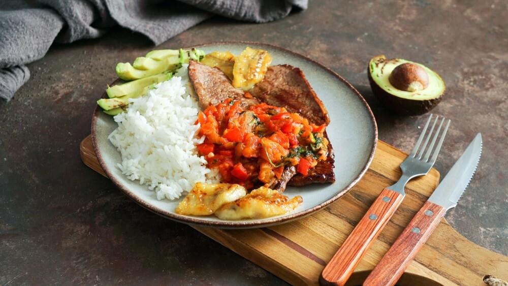 Colombiaans eten. flanksteak of Sobrebarriga en salsa criolla - traditioneel Colombiaans gerecht - biefstuk met tomatensaus, rijst, avocado, bananen friet.