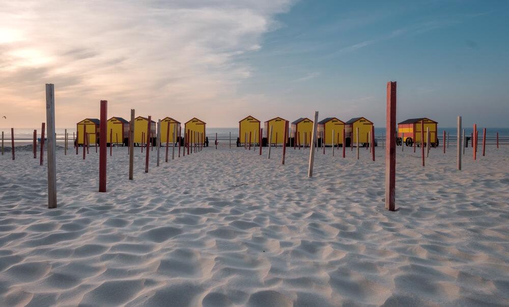 Het strand bij de Panne met zijn gekleurde gele strandhuisjes, België.