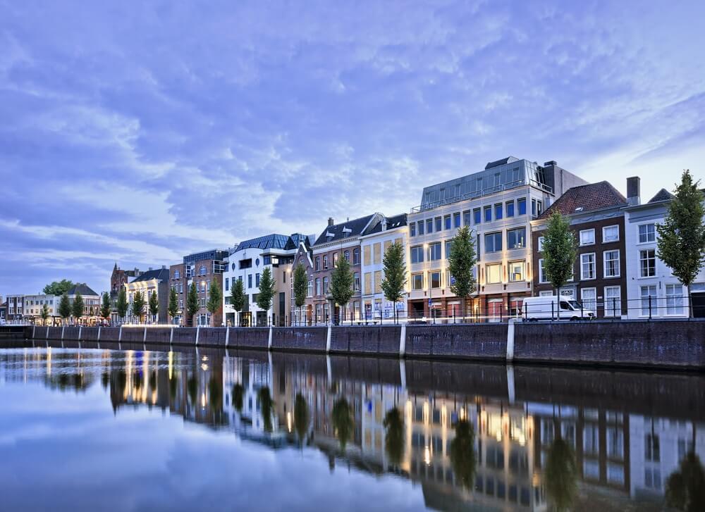 Statige herenhuizen weerspiegeld in een haven bij schemering, Breda, Nederland.