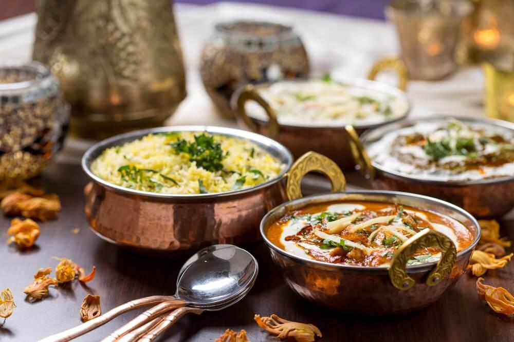 Indiaas gerecht geserveerd in koperen kommen.